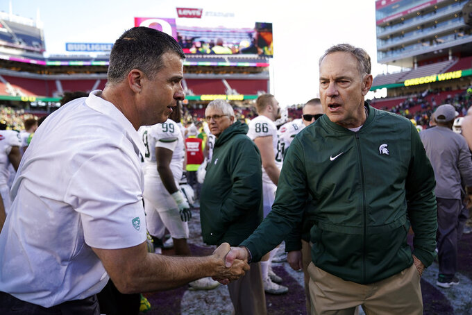 Oregon head coach Mario Cristobal, left, shakes hands with Michigan State head coach Mark Dantonio at midfield after during the Redbox Bowl NCAA college football game Monday, Dec. 31, 2018, in Santa Clara, Calif. (AP Photo/Tony Avelar)