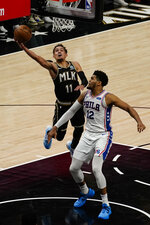 Atlanta Hawks guard Trae Young (11) goes up to shoot against Philadelphia 76ers' Tobias Harris (12) during the second half of Game 6 of an NBA basketball Eastern Conference semifinal series Friday, June 18, 2021, in Atlanta. (AP Photo/John Bazemore)