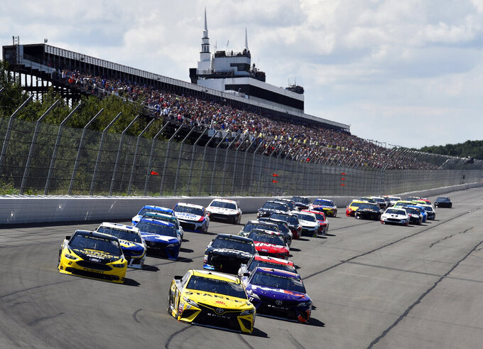 FILE - In this July 29, 2018, file photo, Daniel Suarez (19) leads the field into Turn 1 to start a NASCAR Cup Series auto race, at Pocono Raceway in Long Pond, Pa. NASCAR made the first significant changes to its schedule in years by shuffling the 2020 season into a freshened new sequence that tries to meet the wants of fans to the best of NASCAR's current ability. (AP Photo/Derik Hamilton, File)