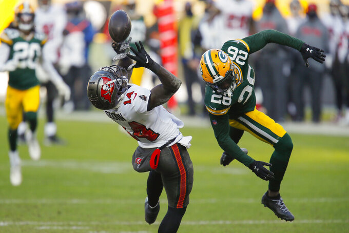 Tampa Bay Buccaneers' Chris Godwin (14) catches a pass against Green Bay Packers' Darnell Savage (26) during the first half of the NFC championship NFL football game in Green Bay, Wis., Sunday, Jan. 24, 2021. (AP Photo/Matt Ludtke)