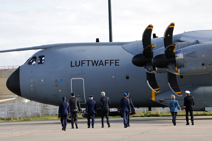 Officials walk towards a German air force airplane after it landed at Lisbon airport, Wednesday, Feb. 3, 2021. The airplane is bringing 26 German army medics along with medical equipment to help out at Portuguese hospitals under stress from the recent increase in COVID-19 hospitalizations. (AP Photo/Armando Franca)
