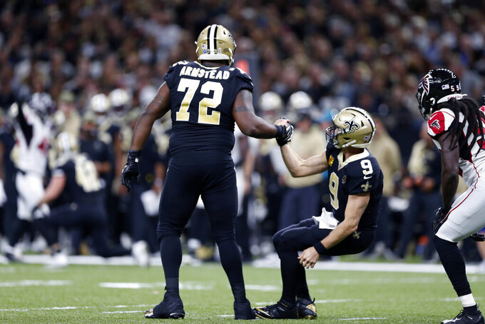 New Orleans Saints offensive tackle Terron Armstead (72) helps up quarterback Drew Brees (9) after he hit the turf in the first half of an NFL football game against the Atlanta Falcons in New Orleans, Sunday, Nov. 10, 2019. (AP Photo/Rusty Costanza)