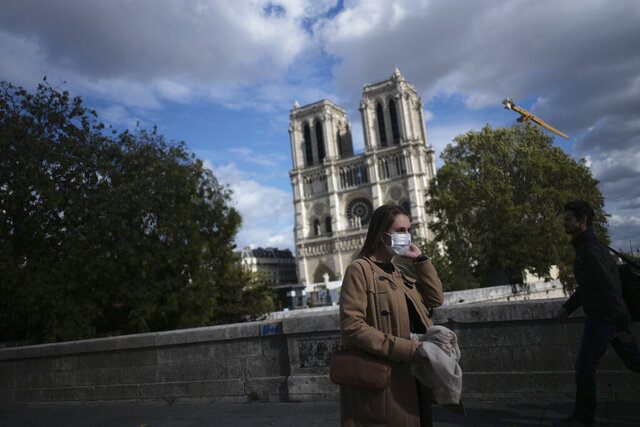 A woman walks by Notre Dame cathedral Saturday Sept.26, 2020 in Paris. While France suffered testing shortages early in the pandemic, ramped-up testing since this summer has helped authorities track a rising tide of infections across the country. More than 15,000 new cases were reported Friday, and the Paris hospital system is starting to delay some non-virus surgeries to free up space for COVID-19 patients. (AP Photo/Lewis Joly)
