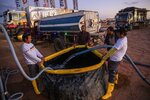 In this Thursday, Jan. 9, 2020 photo, Karcher staffers fill a tank with water to be used for cleaning vehicles at the bivouac of the Dakar Rally in Hail, Saudi Arabia. Formerly known as the Paris-Dakar Rally, the race was created by Thierry Sabine after he got lost in the Libyan desert in 1977. Until 2008, the rallies raced across Africa, but threats in Mauritania led organizers to cancel that year's event and move it to South America. It has now shifted to Saudi Arabia. The race started on Jan. 5 with 560 drivers and co-drivers, some on motorbikes, others in cars or in trucks. Only 41 are taking part in the Original category. (AP Photo/Bernat Armangue)