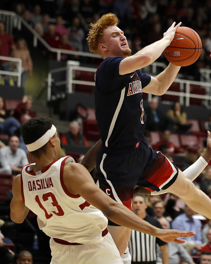 Arizona's Nico Mannion, right, passes the ball away from Stanford's Oscar da Silva (13) during the second half of an NCAA college basketball game Saturday, Feb. 15, 2020, in Stanford, Calif. (AP Photo/Ben Margot)