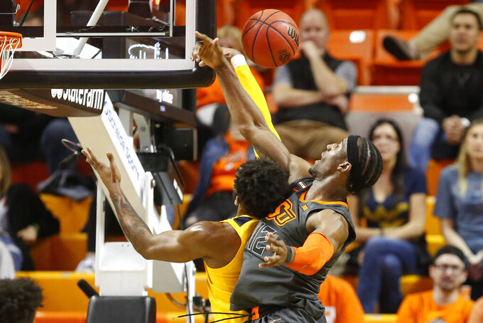 West Virginia forward Derek Culver, left, and Oklahoma State forward Cameron McGriff, right, reach for a rebound in the second half of an NCAA college basketball game in Stillwater, Okla., Monday, Jan. 6, 2020. (AP Photo/Sue Ogrocki)