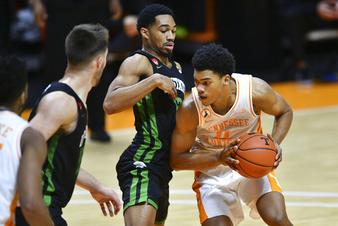 Tennessee's Jaden Springer, right, is guarded by South Carolina-Upstate's Everette Hammond, center, during an NCAA college basketball game Wednesday, Dec. 23, 2020, in Knoxville, Tenn. (Saul Young/Knoxville News Sentinel via AP, Pool)