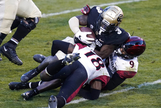 Colorado wide receiver K.D. Nixon is tackled by San Diego State safety Trenton Thompson, front, and safety Tayler Hawkins during the first half of an NCAA college football game Saturday, Nov. 28, 2020, in Boulder, Colo. (AP Photo/David Zalubowski)
