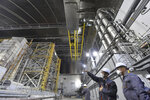 FILE - In this June 1, 2019, file photo, French Foreign Minister Jean-Yves Le Drian, right, listens to an employee inside the New Safe Confinement (NSC) movable enclosure at the nuclear power plant in Chernobyl, Ukraine. A new structure built to confine the Chernobyl reactor at the center of the world's worst nuclear disaster was previewed for the media Tuesday, July 2. (Sergei Supinsky/Pool Photo via AP, File)