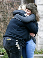 People hug outside the Belmont University Chapel in Nashville at the Janet Ayers Academic Center, where the memorial service for Kyle Yorlets was held Monday, Feb. 11, 2019, after Yorlets, the frontman for the rock band Carverton, was killed during a robbery. Police have charged five juveniles in the case. The memorial service followed a press conference by his fellow Carverton band members.  (Shelley Mays/The Tennessean via AP)