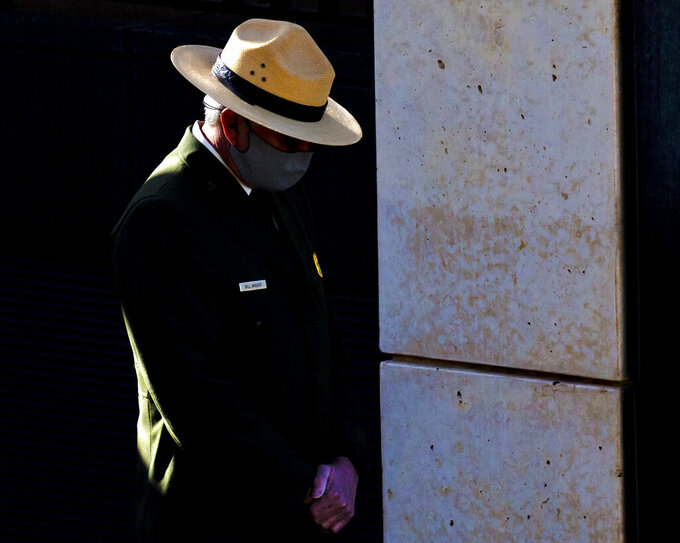 A National Park Ranger lowers his head during the 168 seconds of silence during the 26th Anniversary Remembrance Ceremony at the Oklahoma City National Memorial and Museum in Oklahoma City, Okla on Monday, April 19, 2021. (Chris Landsberger/The Oklahoman via AP)
