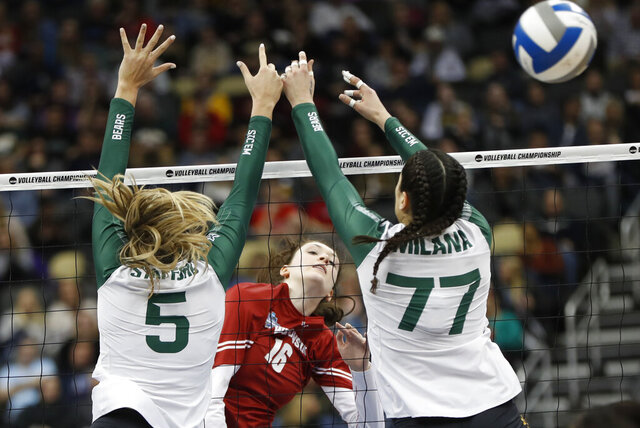 FIEL - Wisconsin's Dana Rettke (16) gets a spike by Baylor's Shelly Stafford (5) and Gia Milana (77) during a semifinal game of the NCAA Div I Women's Volleyball Championships in Pittsburgh, in this Thursday, Dec. 19, 2019, file photo. Wisconsin will open the reconfigured women's volleyball season ranked first in the nation. Women's volleyball will be the first of the NCAA fall sports to play this spring after the COVID-19 pandemic prompted most conferences to cancel or shorten their 2020 fall seasons and the NCAA to call off the national tournament. (AP Photo/Keith Srakocic, FIie)