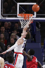 Gonzaga forward Corey Kispert, top, shoots in front of Loyola Marymount guard Eli Scott during the first half of an NCAA college basketball game in Spokane, Wash., Thursday, Feb. 6, 2020. (AP Photo/Young Kwak)