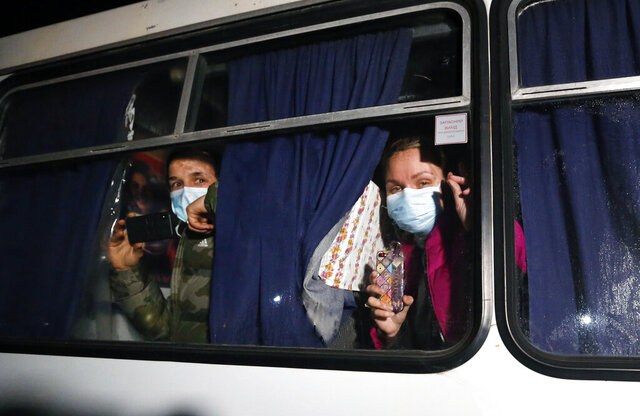 Ukrainian passengers evacuated from the Chinese city of Wuhan, look though a bus window outside Novi Sarzhany, Ukraine, Thursday, Feb. 20, 2020. Several hundred residents in Ukraine's Poltava region protested to stop officials from quarantining the evacuees in their village because they feared becoming infected. Demonstrators put up road blocks and burned tires, while Ukrainian media reported that there were clashes with police, and more than 10 people were detained. (AP Photo/Efrem Lukatsky)