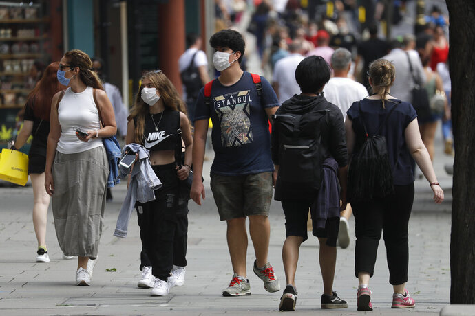 FILE - In this Thursday, Aug. 13, 2020 file photo, shoppers walk along Oxford Street in London. Britain started testing a new smartphone app Thursday to help people find out whether they've been close to someone infected with COVID-19 after security concerns torpedoed an earlier effort to use technology to track the disease. (AP Photo/Kirsty Wigglesworth, File)
