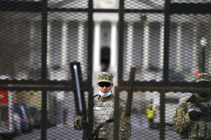 Members of the National Guard stand inside the security fencing at the Capitol ahead of the inauguration of President-elect Joe Biden and Vice President-elect Kamala Harris, Sunday, Jan. 17, 2021 in Washington. (AP Photo/John Minchillo)