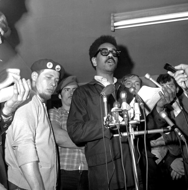 FILE - In this June 4, 1969, file photo, Bobby Rush, deputy defense minister of the Illinois Black Panther party, center, reads a statement at a news conference after an early morning raid on Chicago Panther headquarters by FBI agents. At left is Jose