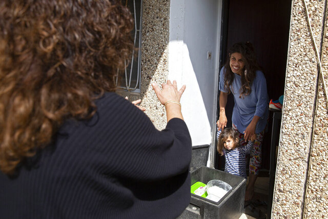In this Monday, April 6, 2020 photo, volunteer Einat Kedem, left, speaks with emergency room doctor Maayan Bacher, after delivering her a home-cooked meal, in the Israeli city of Raanana. More than 10,000 people have responded to Israeli Adi Karmon Scope's Facebook plea to help overworked health-care professionals on the frontline of the country's battle against the coronavirus pandemic. An army of volunteers is doing their grocery shopping, delivering home-cooked meals, babysitting for children and even walking pets. (AP Photo/Sebastian Scheiner)