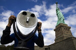FILE - In this Oct. 13, 2013, file photo, the Statue of Liberty looms over a visitor as he uses binoculars to look out onto New York Harbor in New York. (AP Photo/John Minchillo, File)