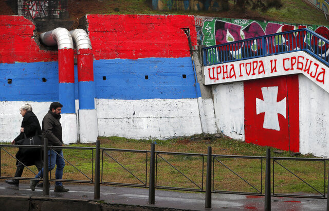 People walk by graffiti showing a Serbian flag, left, and text reading