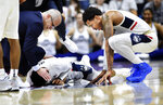 Connecticut's Alterique Gilbert (3) is comforted by Connecticut coach Dan Hurley and Connecticut's Jalen Adams (4) after hurting his previously injured shoulder during the second half of a the team's NCAA college basketball game against Wichita State on Saturday, Jan. 26, 2019, in Storrs, Conn. (AP Photo/Stephen Dunn)