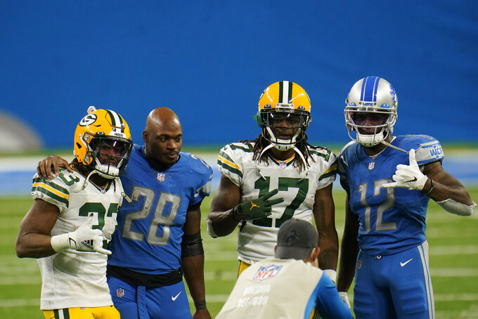 From left, Green Bay Packers running back Aaron Jones (33), Detroit Lions running back Adrian Peterson (28), Packers wide receiver Davante Adams (17) and Lions wide receiver Mohamed Sanu (12) pose for a photographer after their NFL football game, Sunday, Dec. 13, 2020, in Detroit. (AP Photo/Paul Sancya)12#3\