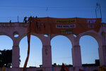 Oil workers hang a banner that reads in Portuguese