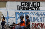 A motorcyclist rides past a wall spray painted with a demand that reads in Spanish:
