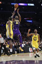 Los Angeles Lakers' LeBron James (23) shoots between Golden State Warriors' Eric Paschall, left, and Alec Burks (8) during the second half of an NBA basketball game Wednesday, Nov. 13, 2019, in Los Angeles. (AP Photo/Marcio Jose Sanchez)