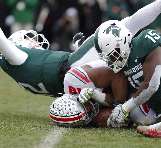 Ohio State's Jonathon Cooper, center, recovers a fumble against Michigan State's Rocky Lombardi, left, and La'Darius Jefferson, right, during the fourth quarter of an NCAA college football game, Saturday, Nov. 10, 2018, in East Lansing, Mich. The ball was fumbled on a pitch from Lombardi to Jefferson. (AP Photo/Al Goldis)