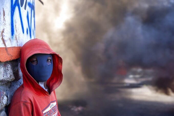 A masked protester stands near a burning barricade during a protest to demand the resignation of Haitian President Jovenel Moise in Port-au-Prince, Haiti, Sunday, Feb. 7, 2021. ( AP Photo/Dieu Nalio Chery)