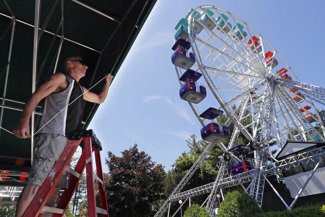 Gary Henderson installs an awning near the Giant Sky Wheel while preparing Canobie Lake Park for guests, Thursday, June 18, 2020 in Salem, New Hampshire. The amusement park plans to reopen on July 16th with capacity limitations and safety precautions for guests and workers as a some of the state restrictions due to the COVID-19 virus outbreak are lifted. (AP Photo/Charles Krupa)