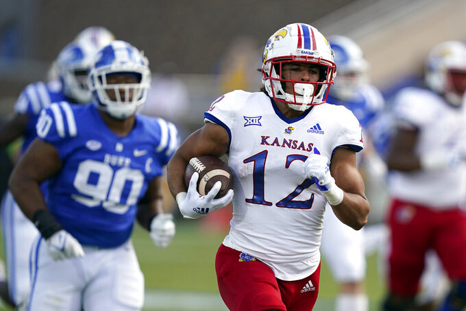Kansas wide receiver Torry Locklin (12) runs for a touchdown as Duke defensive tackle DeWayne Carter (90) pursues during the first half of an NCAA college football game in Durham, N.C., Saturday, Sept. 25, 2021. (AP Photo/Gerry Broome)