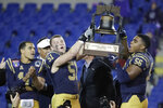 Navy linebacker Paul Carothers (51) and linebacker Nizaire Cromartie (56) lift the trophy after Navy beat Kansas State in the Liberty Bowl NCAA college football game Tuesday, Dec. 31, 2019, in Memphis, Tenn. At left is quarterback Malcolm Perry (10). Navy won 20-17. (AP Photo/Mark Humphrey)