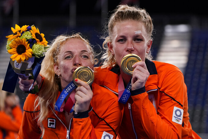 Netherlands' Margot van Geffen, left, and Netherlands' Caia Jacqueline van Maasakker (13) kiss their gold medals after defeating Argentina in the gold medal match at the 2020 Summer Olympics, Friday, Aug. 6, 2021, in Tokyo, Japan. (AP Photo/John Locher)