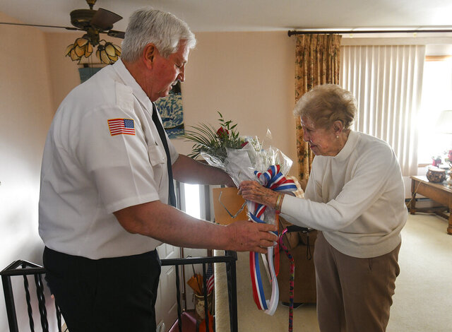 In this Jan. 24, 2020, photo, James Kuchwara, VFW Post #25 commander, gives flowers to Ann Spearmint in Scranton, Pa., to honor her brother, Staff Sgt. Joseph Eugene Prokop, who died in the waning months of World War II. Spearmint, 91, believed for more than seven decades that her brother died when Germans shot down his B-17 bomber near Frankfurt. Historians in Hanau, Germany, have recently discovered that Prokop, then 22, survived the downing of the bomber only to be captured by the Germans and summarily executed after a Gestapo officer learned one of his crewmates was Jewish. (Jason Farmer/The Times-Tribune via AP)
