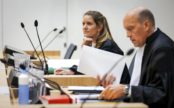 Sabine ten Doesschate, rear, and Boudewijn van Eijck, front, lawyers for one of the four suspects, Russian Oleg Pulatov, are seen as the trial resumed at the high security court building at Schiphol Airport, near Amsterdam, Monday, June 8, 2020, for three Russians and a Ukrainian charged with crimes including murder for their alleged roles in the shooting down of Malaysia Airlines Flight MH17 over eastern Ukraine nearly six years ago. (AP Photo/Robin van Lonkhuijsen, POOL)