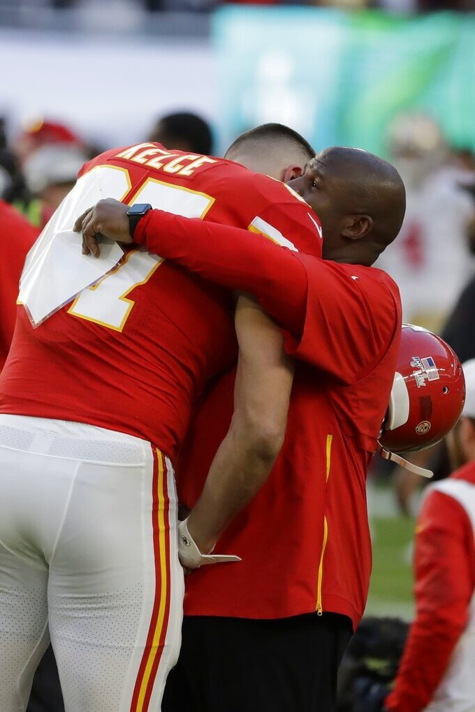 Kansas City Chiefs' Travis Kelce (87) hugs offensive coordinator Eric Bieniemy before the NFL Super Bowl 54 football game between the San Francisco 49ers and Kansas City Chiefs Sunday, Feb. 2, 2020, in Miami Gardens, Fla. (AP Photo/Seth Wenig)