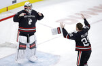 Northeastern goaltender Cayden Primeau, left, and defenseman Eric Williams, right, celebrate after defeating Boston College 4-2 in the NCAA hockey Beanpot tournament final game in Boston, Monday, Feb. 11, 2019. (AP Photo/Charles Krupa)