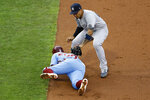 New York Yankees second baseman Gleyber Torres, top, tags out Philadelphia Phillies' Andrew McCutchen on a fielder's choice hit into by Bryce Harper during the third inning of a baseball game Thursday, Aug. 6, 2020, in Philadelphia. Harper was safe at first on the play. (AP Photo/Matt Slocum)