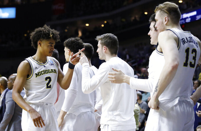 Michigan guard Jordan Poole (2) celebrates with teammates at the end of a second round men's college basketball game against Florida in the NCAA Tournament, Saturday, March 23, 2019, in Des Moines, Iowa. Michigan won 64-49. (AP Photo/Charlie Neibergall)