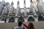 People walk by Notre Dame cathedral Tuesday, Oct. 15, 2019 in Paris. French Culture Minister Franck Riester said the melted, twisted scaffolding atop Notre Dame Cathedral will be removed