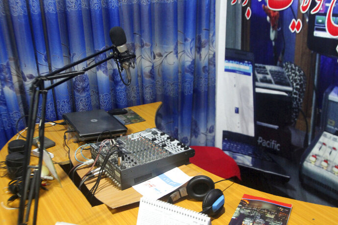 A microphone and a headset stands on the desk of the Samaa local radio Studio in the city of Ghazni province eastern of Kabul, Afghanistan, Tuesday, July 16, 2019. The Samaa local radio eastern Afghanistan was forced to shut down after repeated threats from the area's Taliban commander, the head of the station said on Tuesday. (AP Photo/Rahmatullah Nikzad)
