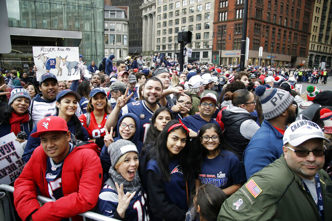 Fans gather near Boston City Hall, Tuesday, Feb. 5, 2019, to watch the New England Patriots football team victory parade through the streets of Boston to celebrate their win over the Los Angeles Rams for their sixth NFL Super Bowl championship. (AP Photo/Elise Amendola)