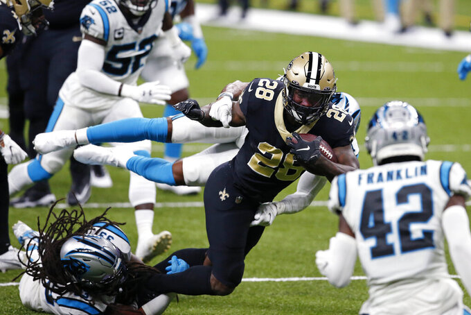 New Orleans Saints running back Latavius Murray (28) is tripped up by Carolina Panthers free safety Tre Boston (33) in the first half of an NFL football game in New Orleans, Sunday, Oct. 25, 2020. (AP Photo/Butch Dill)