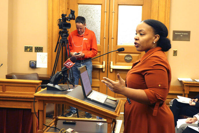 FILE - In this Jan. 28, 2020, file photo, Michele Watley, founder of Shirley's Kitchen Cabinet, testifies in favor of a bill before the Kansas Legislature to ban discrimination based on hairstyles in employment, housing and public accommodations during a committee hearing at the Statehouse in Topeka, Kansas. A growing number of states, like New Mexico, are facing pressure to ban race-based discrimination against hair texture and hairstyles in schools and in the workplace. (AP Photo/John Hanna, File)