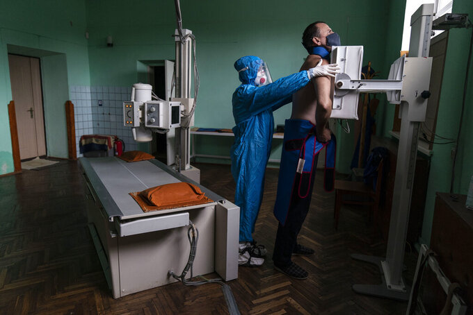 A medic prepares a coronavirus patient for a lung X-ray at a hospital in Stryi, Ukraine, Tuesday, Sept. 29, 2020. Coronavirus infections in Ukraine began surging in late summer, and the ripples are hitting towns in the western part of the country. The government wants to avoid imposing a new lockdown, but officials acknowledge that the rising infections could make it necessary. (AP Photo/Evgeniy Maloletka)
