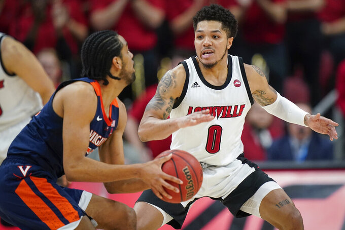 Louisville guard Lamarr Kimble (0) defends against Virginia guard Tomas Woldetensae (53) during the second half of an NCAA college basketball game, Saturday, Feb 8, 2020 in Louisville, Ky. (AP Photo/Bryan Woolston)