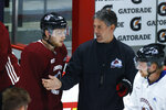 Colorado Avalanche head coach Jared Bednar, right, confers with center Nathan MacKinnon as he takes part in drills during an NHL hockey practice Monday, July 20, 2020, in Denver. (AP Photo/David Zalubowski)