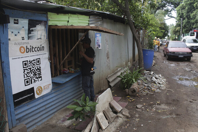 Santos Hilario Galvez, a Salvadoran who works as a builder at the Hope House, an organization that sponsors the use of cryptocurrencies in El Zonte beach, makes a purchase at a small store that accepts Bitcoin, in Tamanique, El Salvador, Wednesday, June 9, 2021. El Salvador's Legislative Assembly has approved legislation making the cryptocurrency Bitcoin legal tender in the country, the first nation to do so, just days after President Nayib Bukele made the proposal at a Bitcoin conference. (AP Photo/Salvador Melendez) (AP Photo/Salvador Melendez)